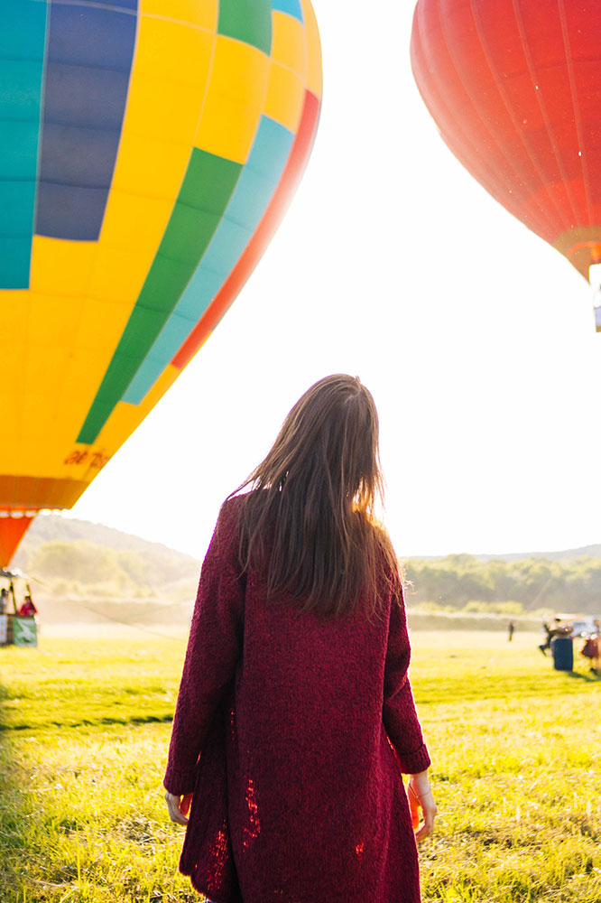 Woman walking through a field containing hot air balloons