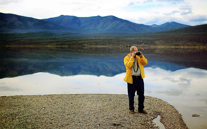 Man is yellow jacket taking photo of a lake