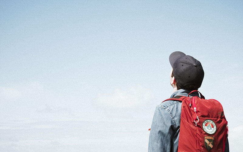 Boy with a cap and red bag on looking into the sky