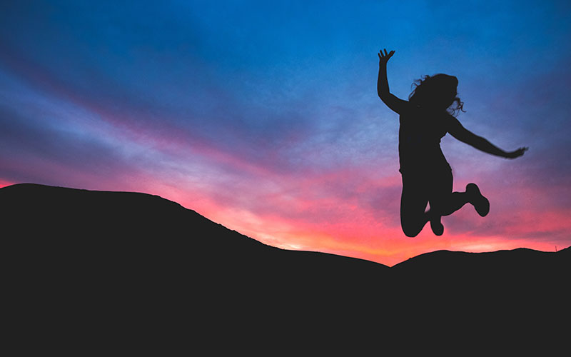 Silhouette of woman jumping in celebration